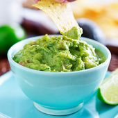 dipping a tortilla chip in a bowl of guacamole