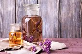 Bottles of herbal tincture and brunch of flowers on a napkin on a wooden table in front of wooden wa