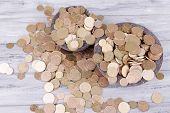 Black round plates full of Ukrainian coins on wooden table