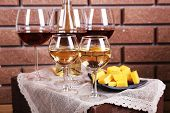 Glasses of wine and cheese on table on brick wall background