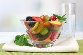 fresh tasty fruit salad on table, on light background