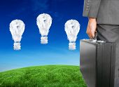 Businessman holding briefcase against cloud light bulbs