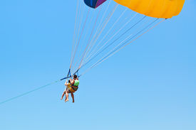 picture of parasailing  - couple people parasailing on parachute in blue sky in summer day - JPG