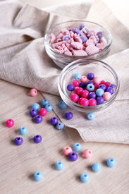 image of crown green bowls  - Different beads in glass bowls on fabric on table - JPG