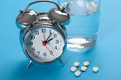 Pills With Glass Of Water And Alarm Clock