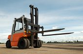 pic of risen  - Forklift loader for warehouse works outdoors with risen forks - JPG