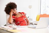 stock photo of studio  - Tired Woman Working At Desk In Design Studio - JPG
