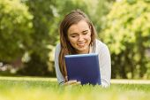 Smiling university student lying and using tablet pc in park at school