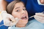 Pediatric dentist using dental explorer and angled mirror in mouth open of a patient