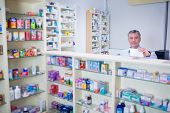 Pharmacist with grey hair holding a prescription in the pharmacy