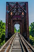 stock photo of trestle bridge  - Vanishing Point View of an Old Railroad Trestle with an Old Iconic Iron Truss Bridge Over the Brazos River - JPG