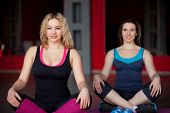 Two Smiling Girls Sit Cross-legged In Fitness Center