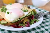 Sandwich with poached eggs, cheese and vegetables on plate on table close up