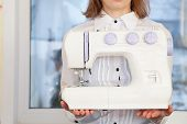 Woman holding sewing machine
