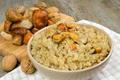 stock photo of porcini  - risotto with porcini mushrooms on wooden table - JPG