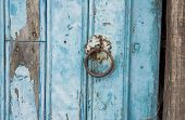 Old run-down blue painted wooden door nails