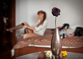 Mysterious redhead putting her stocking with flowers and vase foreground. Sensual woman dressing up