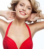 closeup portrait of attractive  caucasian smiling woman blond isolated on white studio shot lips toothy smile face hair head and shoulders looking at camera blue eyes tooth red dress
