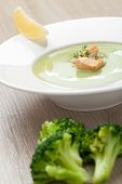foto of water cabbage  - Green cabbage broccoli cream soup puree in white plate served with filleted salmon pieces lemon and theme - JPG