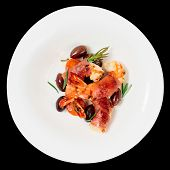 Shrimps with bacon, olives and rosemary in plate, isolated on black