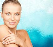 beauty, people and health concept - beautiful young woman with bare shoulders over blue water background