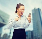 business, technology and education concept - screaming businesswoman with smartphone outside