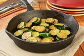 picture of sauteed  - Sauteed zucchini in a cast iron skillet with serving plates - JPG