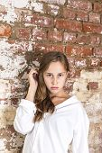 woman in white shirt with grunge brick wall in background