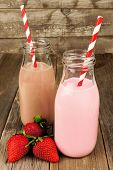 Strawberry and chocolate milk in bottles on wood