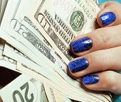 close up fingers with blue creative pattern manicure holding dol