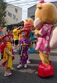 Young Japanese Festival Dancers play with a mascot character