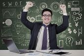 Cheerful Male Manager With Doodles On Blackboard