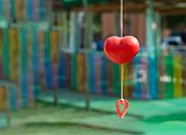 a red heart mobile with blurred background