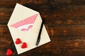 Envelope with hearts and pen on rustic wooden table background