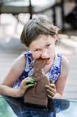 Girl Takes A Bite Of A Chocolate Bunny
