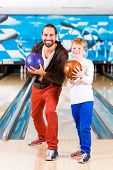 Father and son playing in bowling center