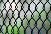 stock photo of chain link fence  - A close up of a green chain link fence on an angle.