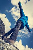 Hiker Catching Balance On Mountain Ridge