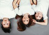 Three teenage sisters lying on the floor