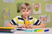 image of schoolboys  - Schoolboy sitting at school desk and drinking orange juice - JPG