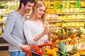 stock photo of bonding  - Happy young couple bonding to each other and smiling while shopping in a food store - JPG