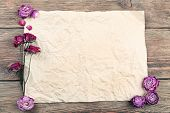 pic of purple rose  - Dried roses on sheet of paper on wooden table - JPG