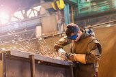 stock photo of goggles  - Young man with protective goggles welding in a factory - JPG