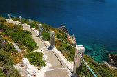 stock photo of greek  - Typical Greek white stairs leading to divers bay on Greek coast - JPG