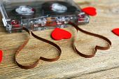 pic of magnetic tape  - Audio cassette with magnetic tape in shape of hearts on wooden background - JPG