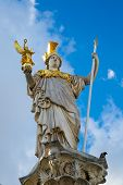 foto of goddess  - Statue and fountain of Pallas Athena Brunnen greek goddess of wisdom in golden helmet in front of Parliament building in Vienna Austria against the blue cloudy sky - JPG