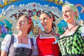 image of visitation  - Friends visiting together Bavarian fair in national costume or Dirndl  - JPG