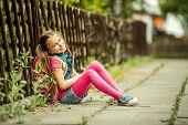 foto of schoolgirl  - Little pretty schoolgirl reading a book sitting on the street - JPG