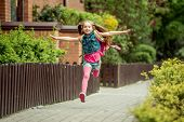stock photo of little school girl  - little girl with a backpack run from school - JPG