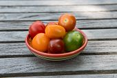 stock photo of ceramic bowl  - Group of tiny tomatoes in a ceramic bowl on a wooden surface - JPG